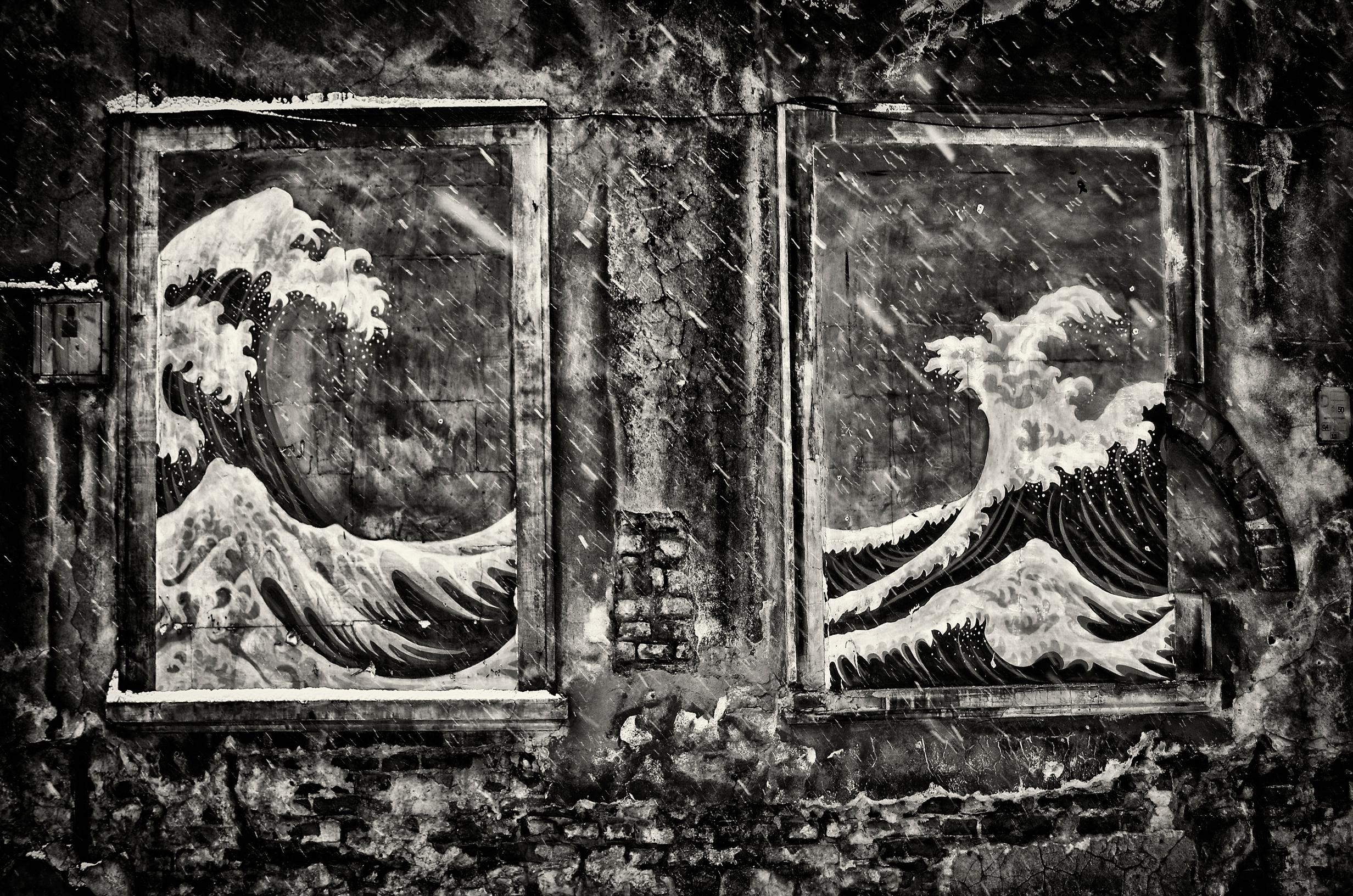 Czarno-biała fotografia zobrazem wzburzonych fal ipadającym deszczem.