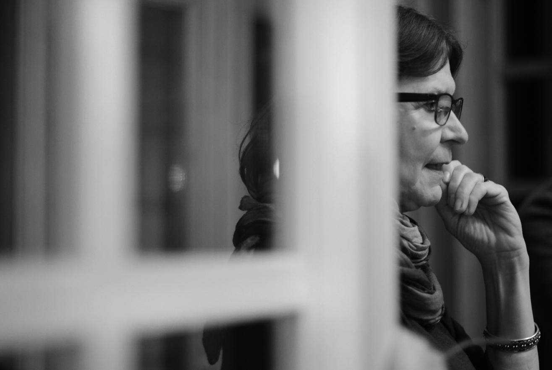 Czarno-białe zdjęcie kobiety zza framugi okna.