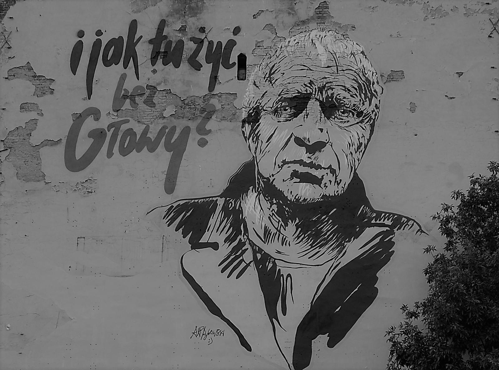 Czarno-białe zdjęcie napisu irysunku mężczyzny naścianie bloku.