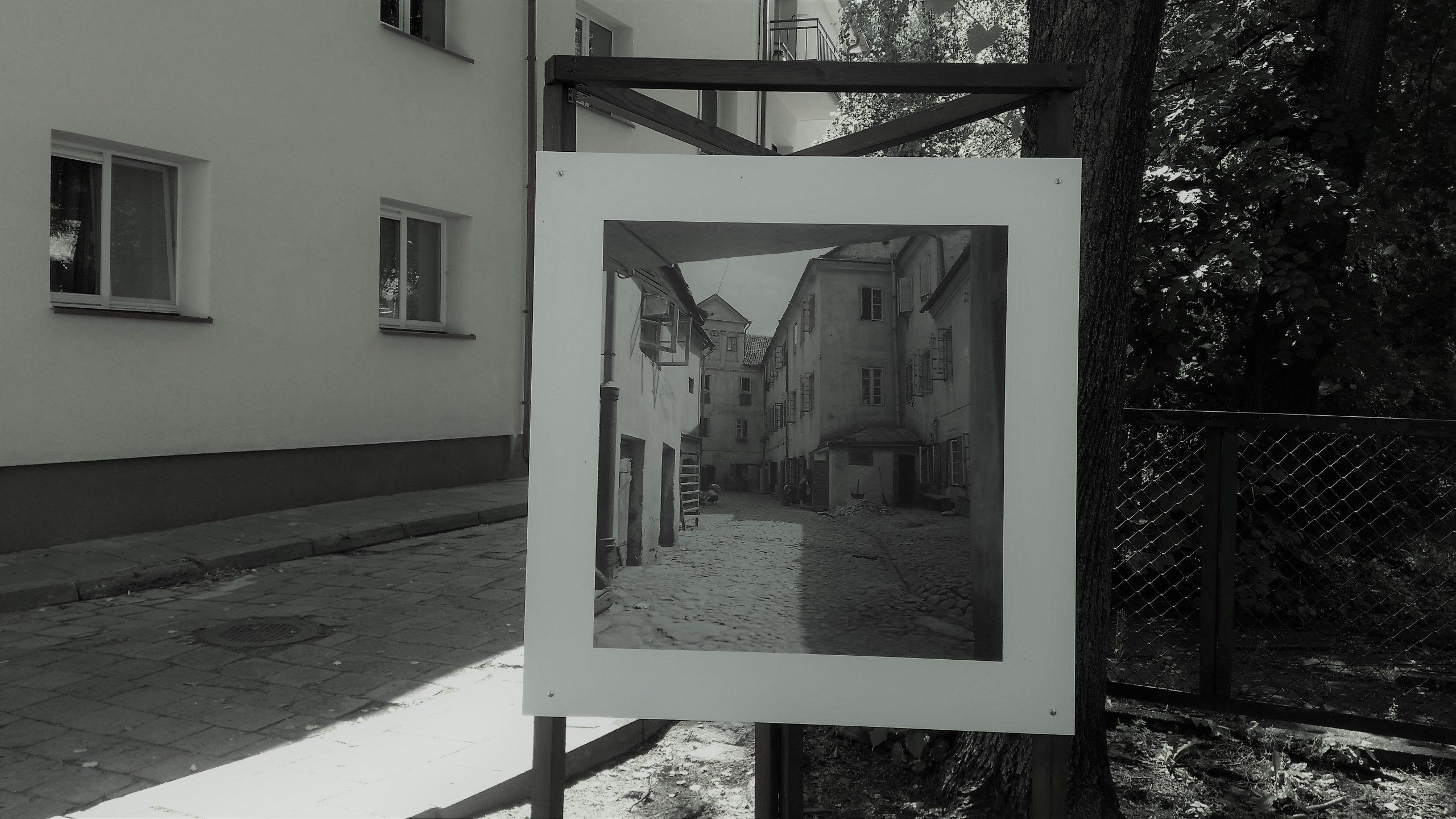 Czarno-biała fotografia podwórka wbiąłej ramie, wyeksponowane stare zdjęcie wteraźniejszej przestrzeni miejskiej.