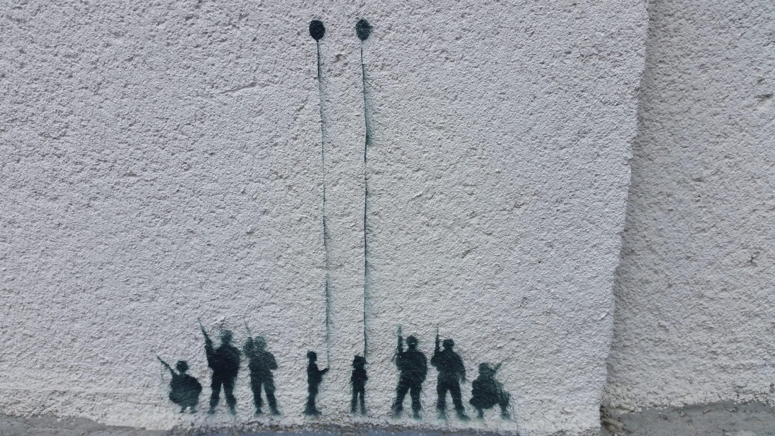 Na szarym murze sprayem namalowane cienie żołnierzy zkarabinami iwśrodku dwojga dzieci zbalonikami.